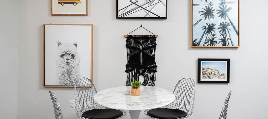 marble dining table with metal chairs with black seat cushions and art on the wall